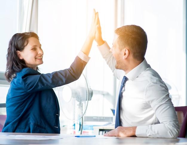 Onderneemster twee en zakenman die hallo-vijf in het bureau geven Gratis Foto