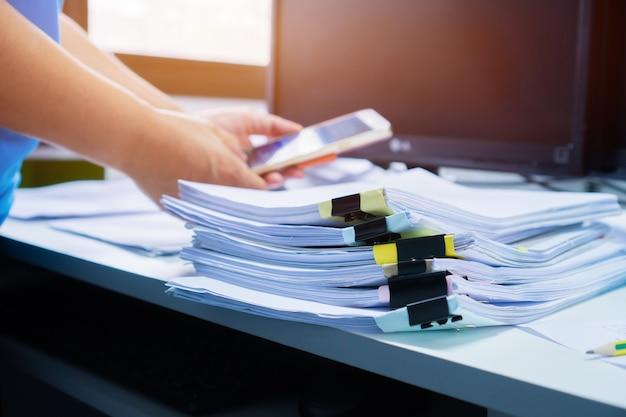Onderneemsterhanden die in stapels document dossiers werken Premium Foto