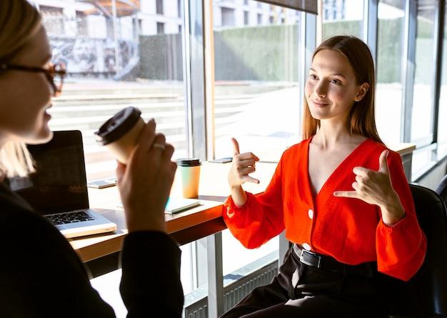 Onderneemsters die gebarentaal gebruiken op het werk terwijl ze koffie drinken Gratis Foto