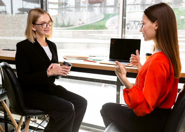 Onderneemsters die op het werk gebarentaal gebruiken om te communiceren Gratis Foto