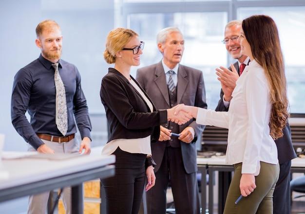 Ondernemers die twee het glimlachen onderneemster het schudden handen toejuichen Gratis Foto