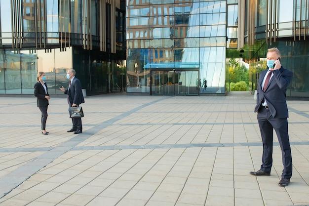 Ondernemers dragen maskers en pakken, praten op kantoorgebouw, spreken op mobiel, project met elkaar bespreken. kopieer ruimte, volledige lengte. bedrijfs- en epidemisch concept Gratis Foto