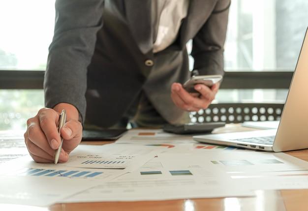 Ondernemers gebruiken pen, laptop en mobiele telefoon plannen een marketingplan om de werkkwaliteit te verbeteren. Premium Foto