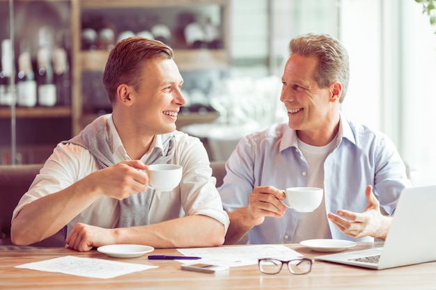 Ondernemers in vrijetijdskleding drinken koffie. Premium Foto