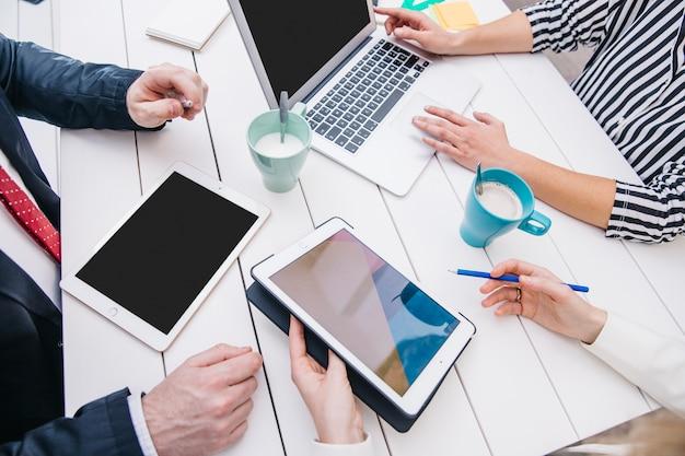 Ondernemers met apparaten aan tafel Gratis Foto