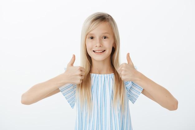 Ondersteunende kleine vriend wil vrienden aanmoedigen. gelukkig positief schattig meisje met blond haar, duimen opsteken en goedkeuring geven, breed glimlachend terwijl ze van geweldig idee houdt, staande over grijze muur Gratis Foto