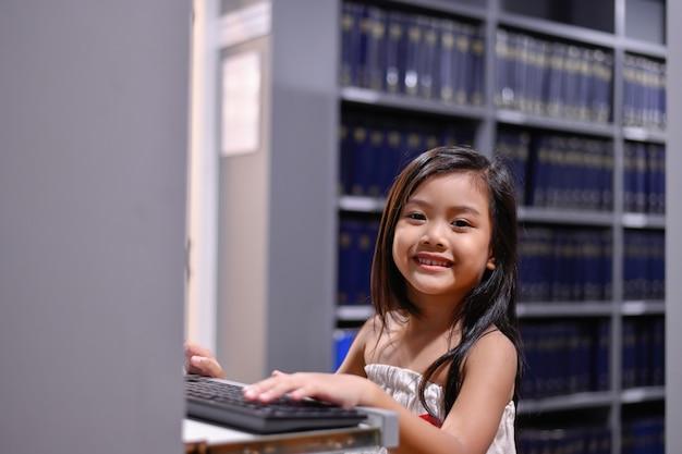 Onderwijs concepten. het meisje studeert in de bibliotheek. mooie meisjes zijn blij leren. Premium Foto