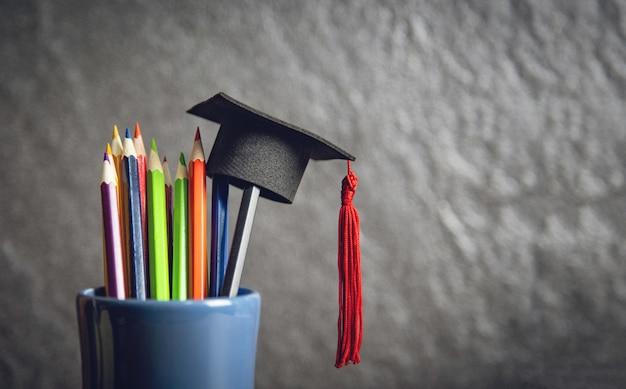 Onderwijs en terug naar school concept met afstuderen cap op potloden kleur in een etui Premium Foto