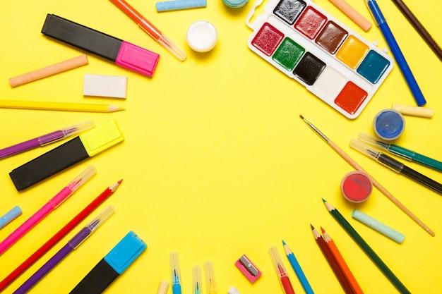 Onderwijs en terug naar school-concept. schoollevering voor het trekken op een gele achtergrond. bovenaanzicht, plat leggen. Premium Foto