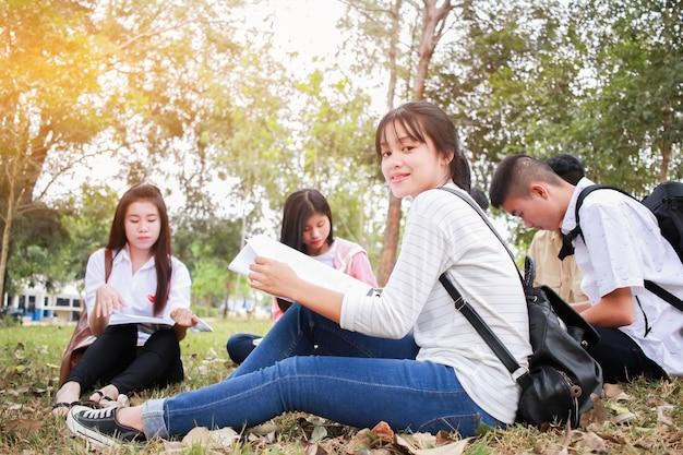Onderwijs het leren studie openluchtconcept: zekere aziatische studentengroepen die gelezen boek zitten Premium Foto