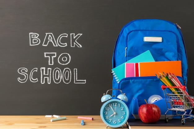 Onderwijs of terug naar schoolconcept, rugzak en kantoorbehoeftenlevering op klaslokaalbureau met bordachtergrond. Premium Foto
