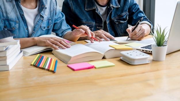 Onderwijs, onderwijs, leren, technologie en mensen concept. twee middelbare schoolstudenten of klasgenoten met hulpvriend homeworks die in klaslokaal, de boeken van de privé-leraar met vrienden leren Premium Foto