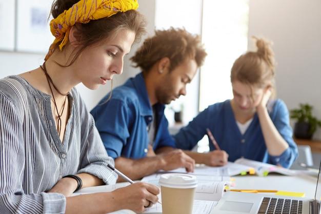 Onderwijs, universiteit en mensen concept. team van vriendelijke studenten werken samen op zoek met serieuze uitdrukkingen in hun schriften schrijven met potloden met behulp van laptopcomputer voor studie Gratis Foto
