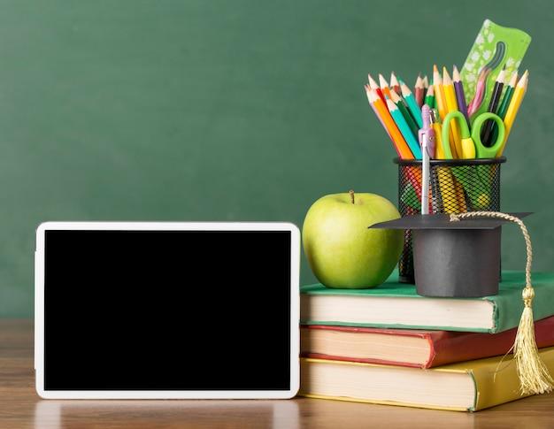 Onderwijsdagassortiment op een tafel met een tablet Gratis Foto