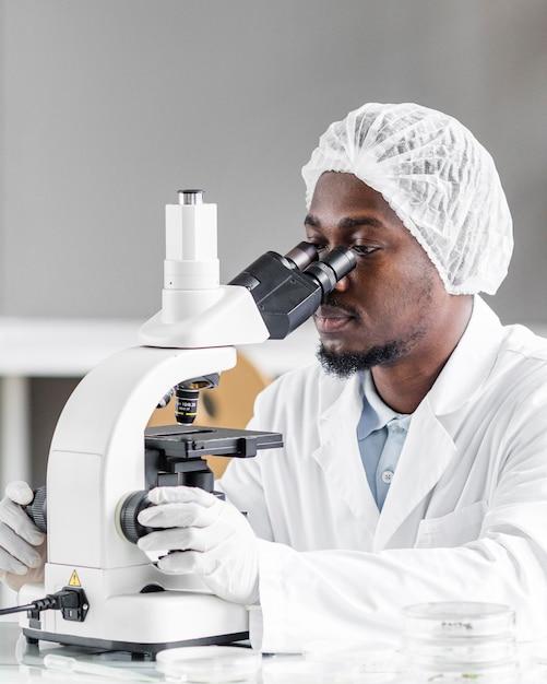 Onderzoeker in het biotechnologielaboratorium met microscoop Premium Foto