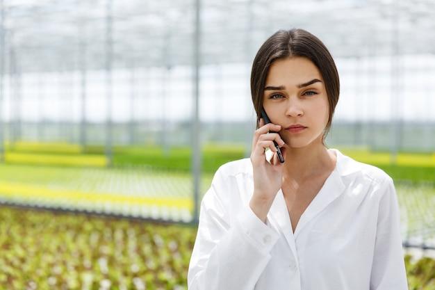 Onderzoeker praat aan de telefoon lopen rond een kas Gratis Foto
