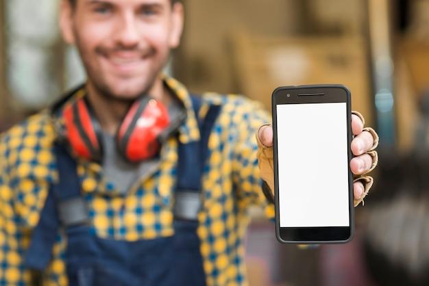Onduidelijk beeldportret van een mannelijke timmerman die zijn smartphone tonen die het witte scherm tonen Gratis Foto