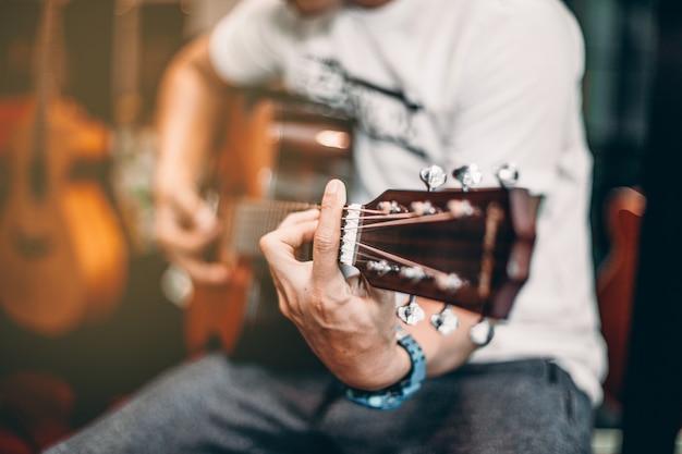 One man in wit t-shirt speelt muziek door gitaar akoestisch Premium Foto