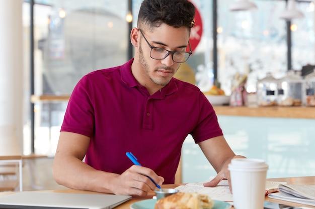 Onervaren jonge mannelijke werknemer doet op afstand werk, houdt een blauwe pen vast, schrijft records of herinnert een notitie in het notitieblok, maakt plannen voor volgende week. student bereidt zich voor op college examen, zit in restaurant Gratis Foto