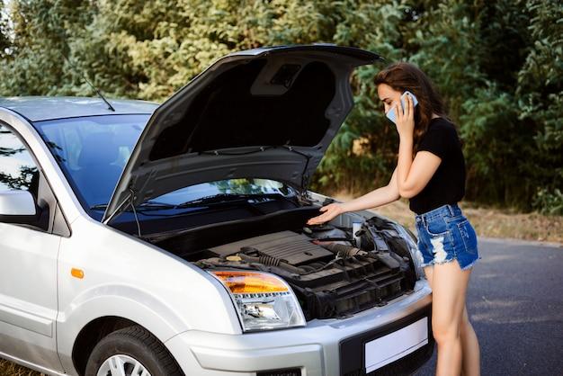Onervaren meisje belt vrienden om advies te krijgen over hoe een kapotte auto onderweg te repareren en thuis te komen, legt uit wat er is gebeurd Premium Foto