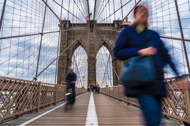 Ongedefinieerde passagier en toerist wandelen en fietsen op de brooklyn bridge. Premium Foto