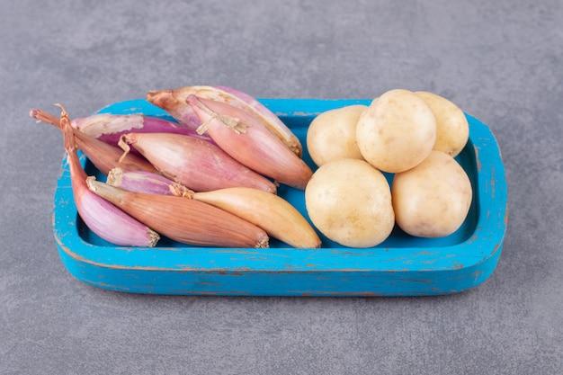 Ongekookte aardappelen met knoflook in een blauwe houten plank. Gratis Foto