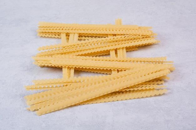 Ongekookte lange pasta op stenen oppervlak Gratis Foto