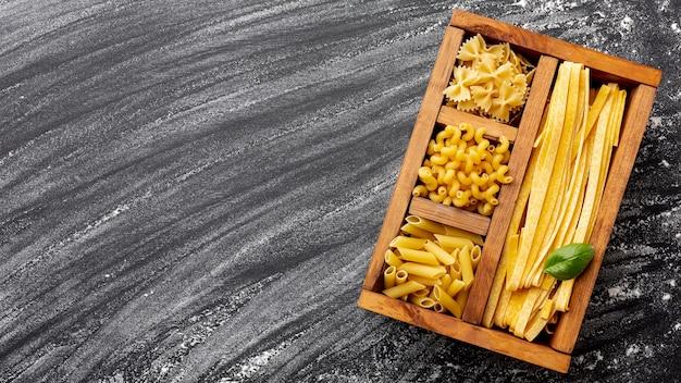 Ongekookte pasta in houten doos met kopie ruimte Gratis Foto