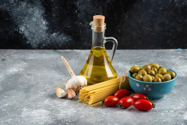 Ongekookte pasta, olie en verse groenten op marmeren tafel. Gratis Foto