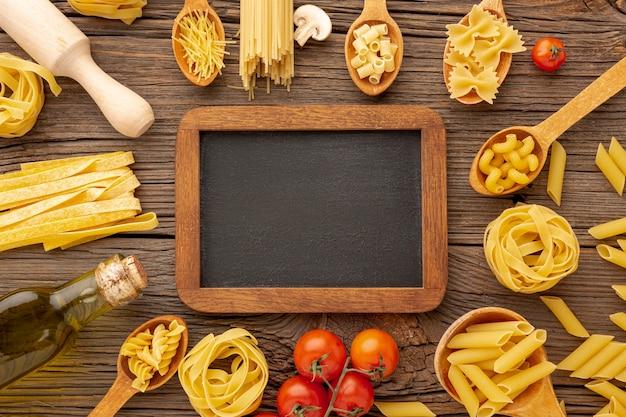 Ongekookte pasta olijfolie en tomaten met schoolbord mock-up Gratis Foto