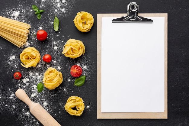 Ongekookte tagliatellespaghetti op zwarte achtergrond met tomatendeegrol en klembordmodel Gratis Foto