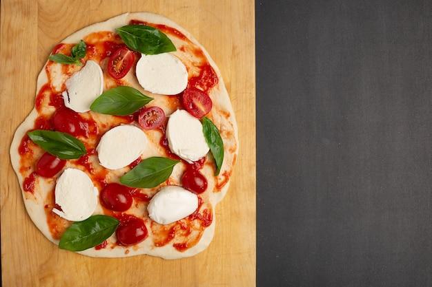 Ongekookte zelfgemaakte pizza op snijplank op donkere achtergrond Premium Foto