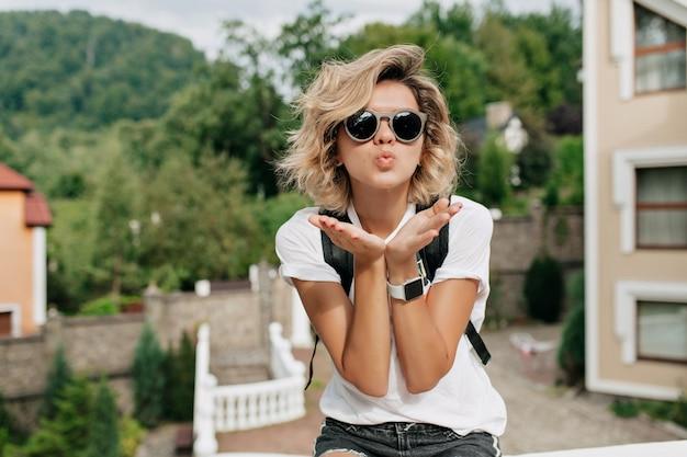 Ongelooflijk effectief charmant meisje met kort krullend kapsel in zwarte zonnebril die een kus verzendt Gratis Foto