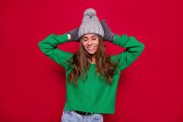 Ongelooflijk meisje draagt groene trui nad grijze winter pet met plezier met meer dan rode achtergrond met confetti. nieuwjaarscadeaus, verjaardag vieren, positieve emoties uiten Gratis Foto