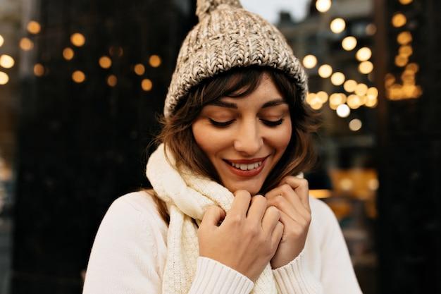 Ongelooflijke charmante dame in gebreide witte muts en gebreide trui lachend Gratis Foto