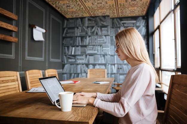 Ongelooflijke jonge vrouwenzitting dichtbij koffie terwijl het werken Gratis Foto