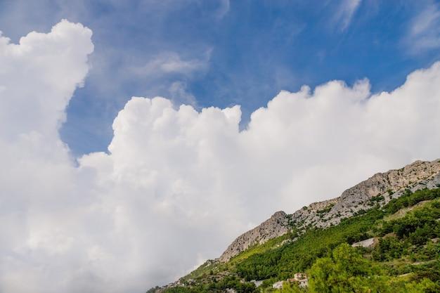 Ongelooflijke witte grote wolk en bergen in brela, kroatië Premium Foto