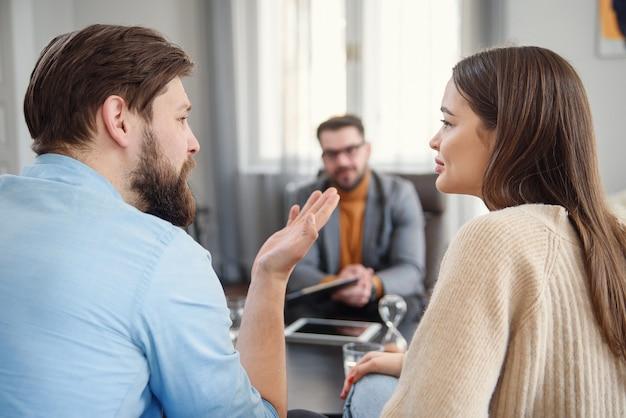 Ongelukkig paar ruzie, ruzie, onenigheid op het kantoor van psychologen, gefrustreerd jong gezin bespreken relatieproblemen met hun therapeut Premium Foto