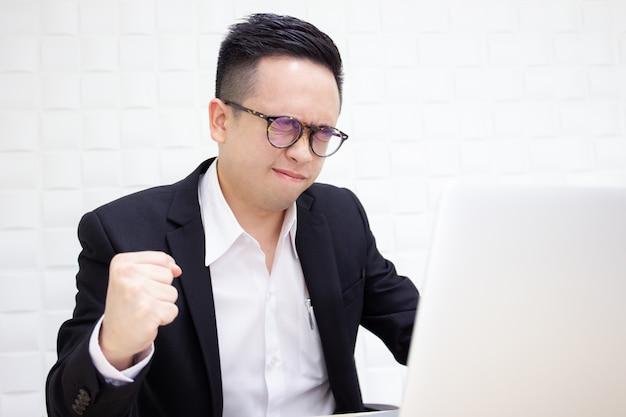 Ongelukkige aziatische zakenman die langdurig hard werkt. Premium Foto