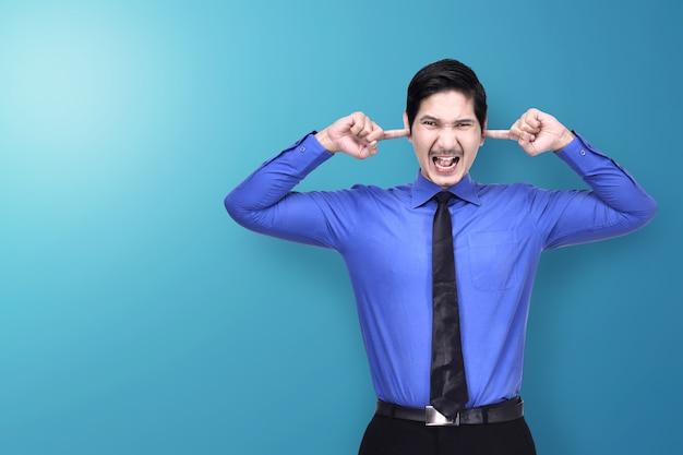 Ongelukkige aziatische zakenman die zijn oren behandelt met hand Premium Foto