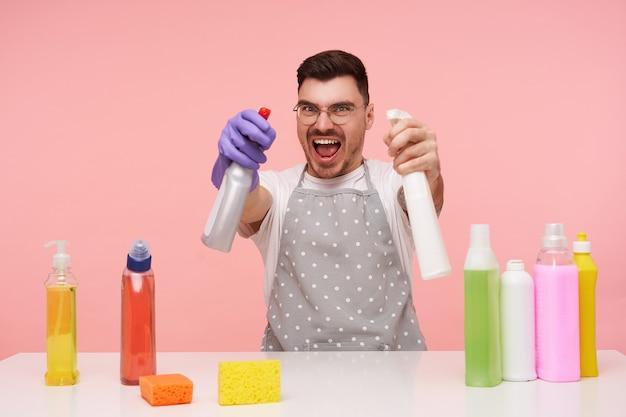Ongelukkige jonge mooie brunette man met kort kapsel kijkt vreugdevol terwijl hij zijn handen opheft met huishoudelijke chemicaliën, plezier maakt tijdens het schoonmaken van huis, geïsoleerd op roze Gratis Foto