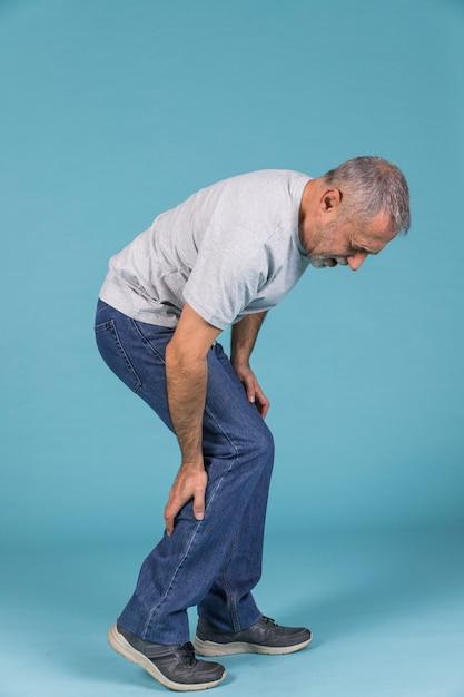 Ongelukkige man die aan strenge pijn op blauw behang lijdt Gratis Foto
