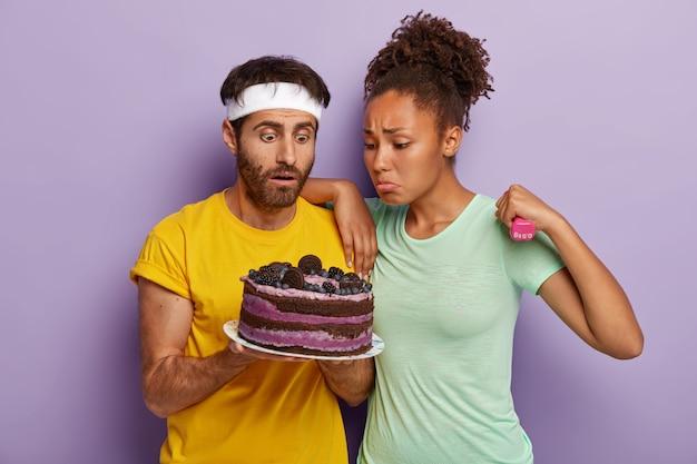Ongelukkige sportieve diverse jonge vrouw en man kijken met verleiding naar heerlijke cake, wil eten maar beseffen dat het schadelijk is, trainen met halters, gekleed in vrijetijdskleding Gratis Foto
