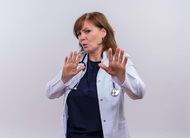 Ongenoegen vrouw arts van middelbare leeftijd die medische mantel en stethoscoop draagt ?? die stopgebaar op geïsoleerde witte achtergrond met exemplaarruimte doet Gratis Foto