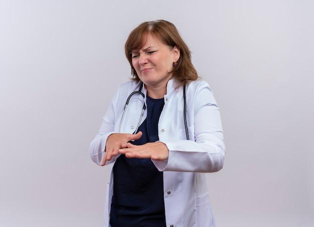 Ongenoegen vrouw arts van middelbare leeftijd die medische mantel en stethoscoop opheffende handen op geïsoleerde witte achtergrond met exemplaarruimte draagt Gratis Foto