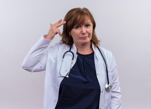 Ongenoegen vrouw van middelbare leeftijd arts die medische mantel en stethoscoop draagt ?? die hand dichtbij hoofd op geïsoleerde witte achtergrond zet Gratis Foto