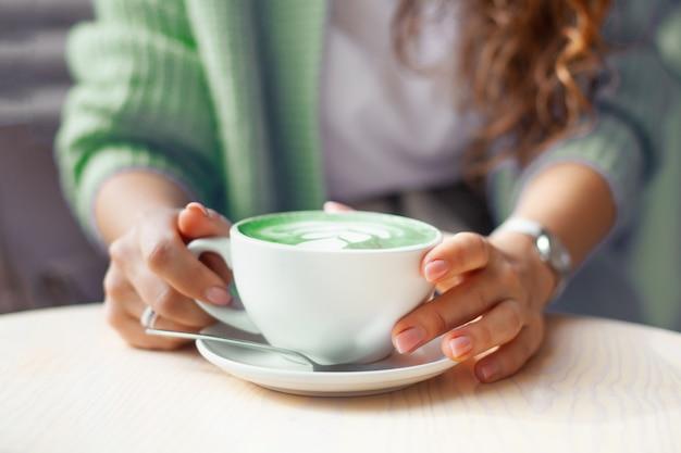 Ongericht vrouw handen met kopje hete vlinder erwt latte of blauwe spirulina latte op houten tafel. biologische gezonde en trendy drank. welzijn en ontgiftingsconcept. kopieer ruimte. Premium Foto