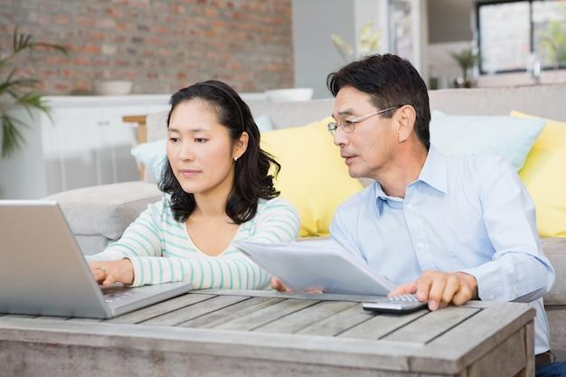 Ongerust gemaakt paar die rekeningen in de woonkamer controleren Premium Foto