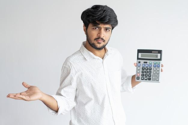 Ongerust gemaakte indische bedrijfsmens die en calculator houdt toont Gratis Foto