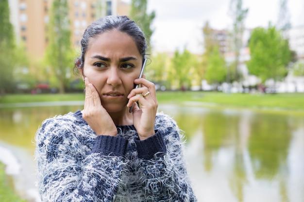 Ongerust gemaakte jonge vrouw die op smartphone in stadspark spreekt Gratis Foto